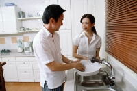 Couple in kitchen, man washing dishes, woman next to him - Alex Microstock02