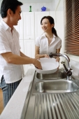 Couple in kitchen, man washing dishes, woman standing next to him, smiling - Alex Microstock02