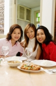 Three women sitting at restaurant table, smiling - Alex Microstock02