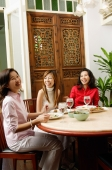 Three women having a meal at restaurant, laughing - Alex Microstock02