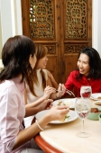 Three women in restaurant, talking - Alex Microstock02