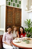 Three women at a restaurant sitting, looking at camera - Alex Microstock02
