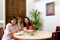 Three women sitting at a restaurant with food on table - Alex Microstock02