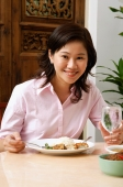 Woman in pink blouse having a meal, looking at camera - Alex Microstock02