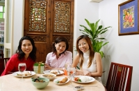 Women sitting at table smiling at camera, portrait - Alex Microstock02
