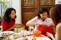 Woman unwrapping gifts with friends - Alex Microstock02