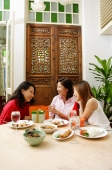Three women in restaurant, talking and laughing - Alex Microstock02