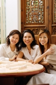 Three women sitting side by side, smiling - Alex Microstock02