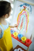 Young girl standing in front of rainbow painting on easel - Alex Microstock02