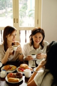 Three women sitting in cafe, having tea - Alex Microstock02