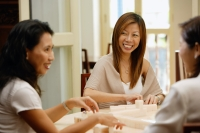 Women sitting around table, playing mahjong - Alex Microstock02