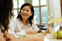 Woman in restaurant smiling at person next to her - Alex Microstock02