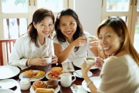 Three women having tea at cafe, smiling at camera - Alex Microstock02