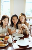 Three women smiling at camera, holding cups, portrait - Alex Microstock02