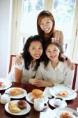Three women in cafe, smiling at camera, portrait - Alex Microstock02