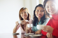Women sitting at table with cups and saucers, looking at camera - Alex Microstock02