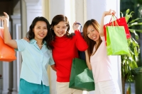 Three women carrying shopping bags, smiling at camera, portrait - Alex Microstock02