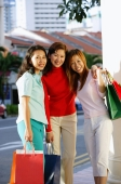 Three women standing, carrying shopping bags, smiling at camera - Alex Microstock02