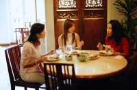 Three women having a meal at restaurant, talking - Alex Microstock02