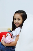 Young girl holding a doll, smiling at camera - Alex Microstock02