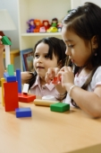 Two girls side by side, playing with building blocks - Alex Microstock02