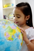 Young girl looking at globe, smiling - Alex Microstock02