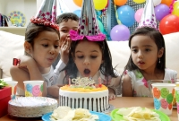 Birthday party, young girl blowing candles on cake - Alex Microstock02