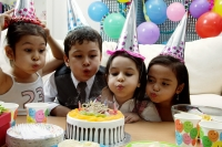 Children celebrating birthday, blowing candles on cake - Alex Microstock02