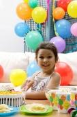 Girl cutting birthday cake, looking at camera - Alex Microstock02