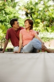 Couple sitting on floor, side by side, looking at each other - Alex Microstock02