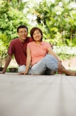 Couple sitting on floor, side by side, looking at camera - Alex Microstock02