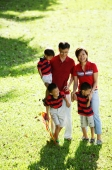 Family with three boys, standing on field, looking at camera - Alex Microstock02