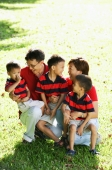 Family with three boys on field, smiling at each other - Alex Microstock02