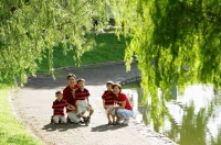 Family with three boys outdoors in park, smiling at camera - Alex Microstock02
