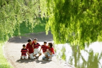Family with three boys outdoors in park, tree branches in foreground - Alex Microstock02