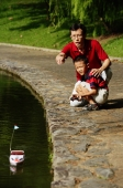 Father and son playing with remote control boat - Alex Microstock02