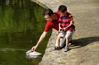 Father and son playing with remote control boat, father reaching for boat - Alex Microstock02