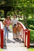 Family with three boys in park, standing on bridge, smiling at camera - Alex Microstock02