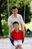 Father and son in playground, father pushing son on swing - Alex Microstock02
