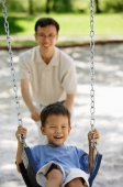 Boy on swing, father pushing him - Alex Microstock02