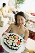 Woman holding up plate of sushi, looking at camera, people in the background - Alex Microstock02