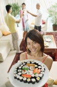 Woman holding up plate of sushi, smiling at camera, people in the background - Alex Microstock02