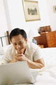 Man in bedroom, looking at laptop, hands clasped, under chin - Alex Microstock02