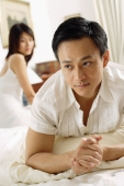 Couple in bedroom, man lying down, looking away, woman sitting behind him - Alex Microstock02