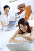 Couple in bedroom, woman with laptop, man sitting behind her reading newspaper - Alex Microstock02