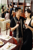 Couple in dining room, holding wine glasses, people in the background - Alex Microstock02