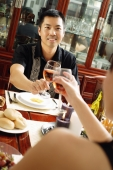 Couple toasting wine glasses across dining table, over the shoulder view - Alex Microstock02