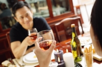 Couple holding wine glasses, sitting opposite each other - Alex Microstock02