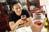 Man holding wine glass, smiling at person across from him - Alex Microstock02