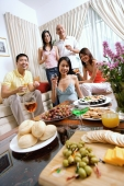Adults in living room, having a party, smiling at camera, food in the foreground - Alex Microstock02